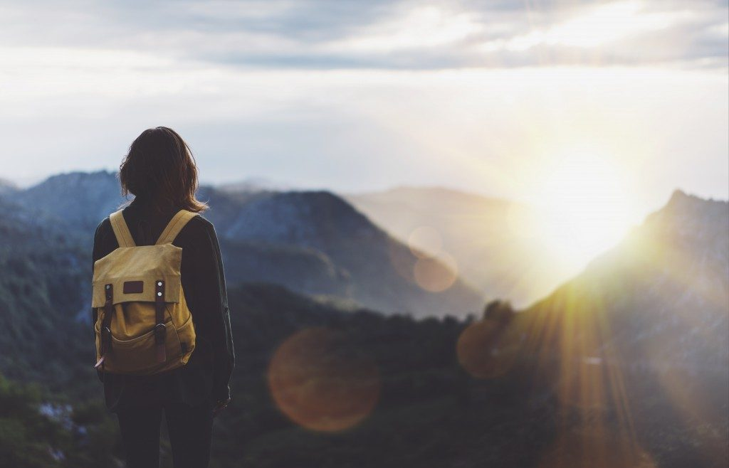 ImageHipster young girl with backpack enjoying sunset on peak of foggy mountain
