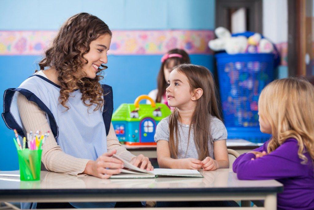preschool teacher beside her student