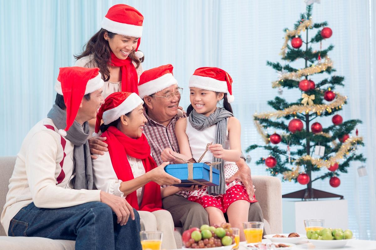 Family by the Christmas tree wearing santa hats