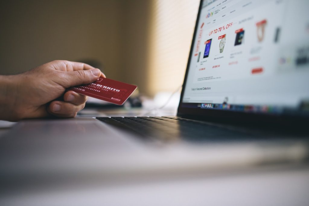online shopping laptop holding credit card