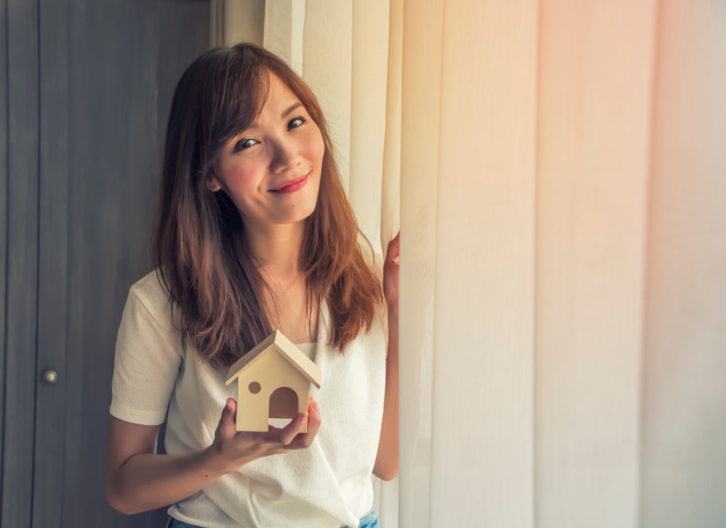 woman holding a toy house