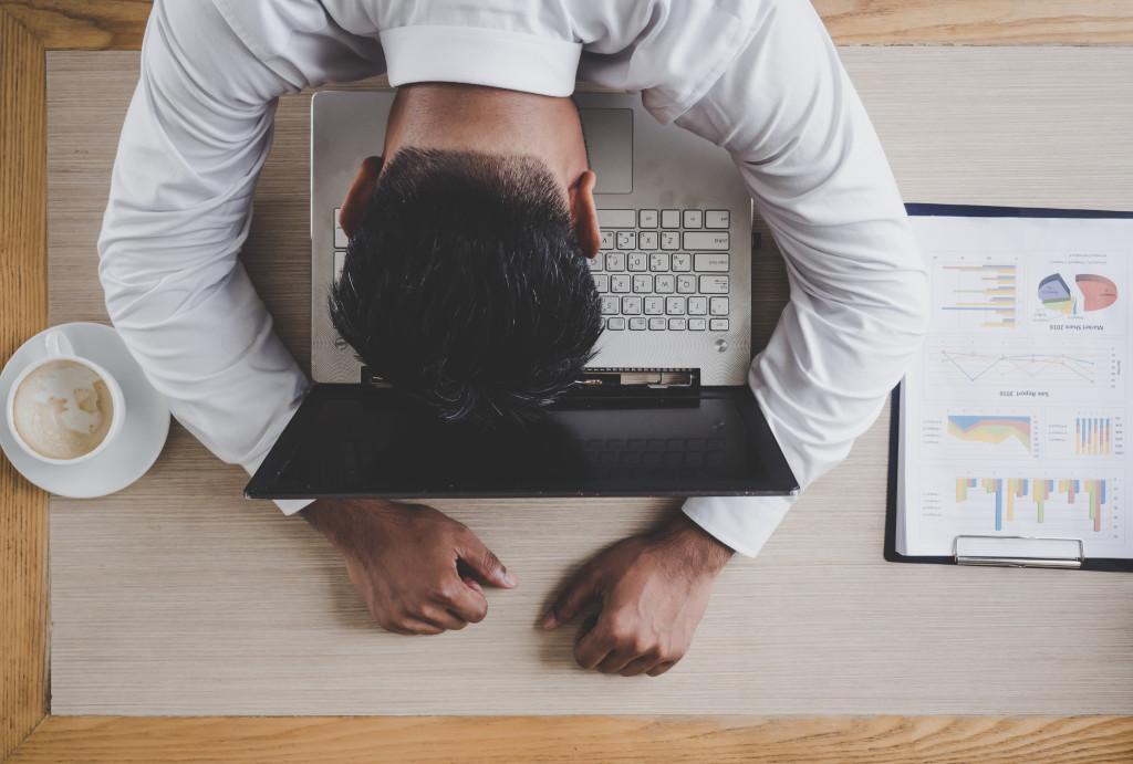 man slumped on laptop