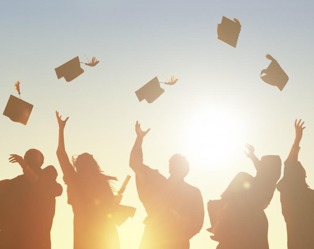 graduates tossing their caps